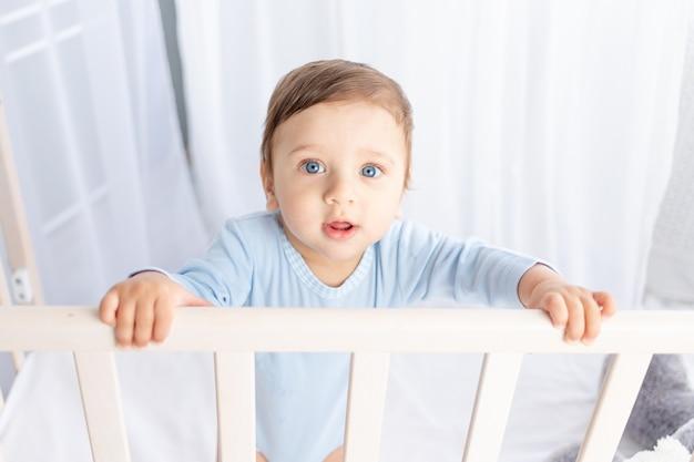 Schattige babyjongen met grote blauwe ogen in de wieg in de kinderkamer, portret