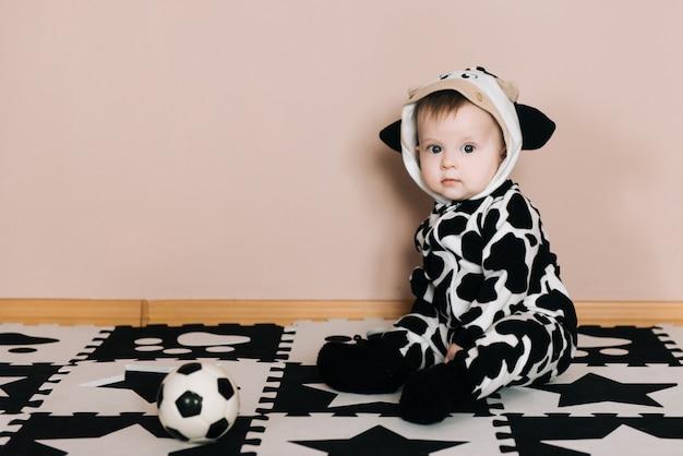 Schattige babyjongen met voetbal bal zit op zwart-witte kleding, sport, actieve levensstijl