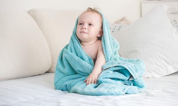 Schattige babyjongen na het douchen bedekt met blauwe deken op de bank
