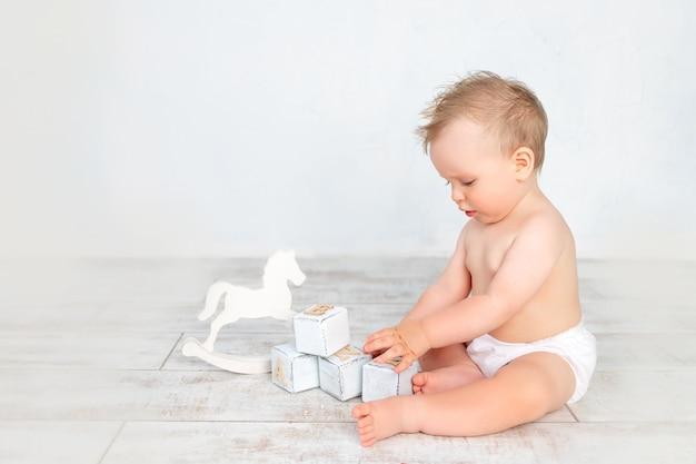 Schattige babyjongen op een witte achtergrond met een kapsel en grote blauwe ogen in luiers op een witte achtergrond met een kapsel spelen met houten peren