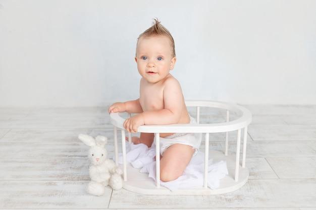 Schattige babyjongen op een witte achtergrond met een kapsel en grote blauwe ogen in luiers op een witte achtergrond met een kapsel zittend in een houten mand