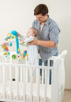 Schattige babyjongen staat in bed en speelt met carrousel met zijn vader