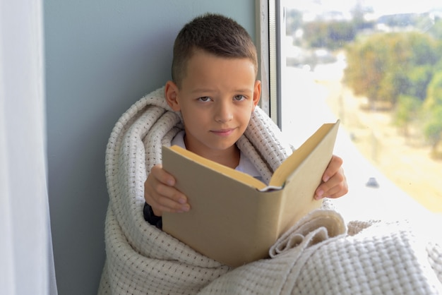 Schattige babyjongen zit bij het raam en leest een boek in de kamer thuis prachtige herfstnatuur