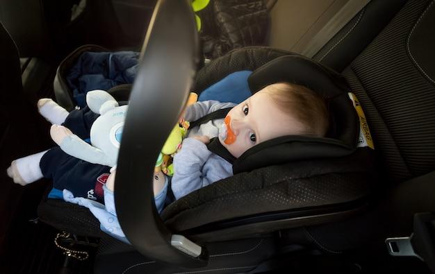 Schattige babyjongen zit in babyveiligheidszitje in de auto