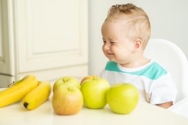 Schattige babyjongen zittend aan de tafel in kinderstoel appel eten op witte keuken