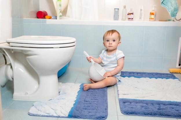 Schattige babyjongen zittend op de vloer in de badkamer