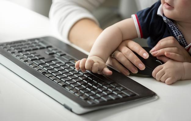 Schattige babyjongen zittend op moeders schoot terwijl ze op de computer werkt