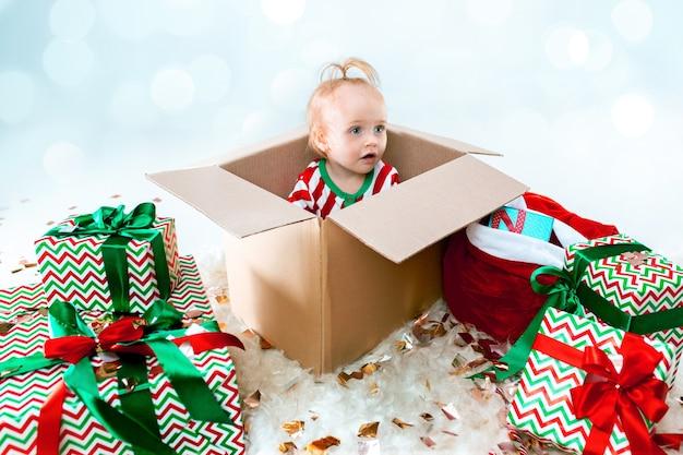Schattige babymeisje 1 jaar oud zittend in doos tijdens kerstmis