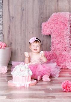 Schattige babymeisje eerste verjaardagstaart eten.
