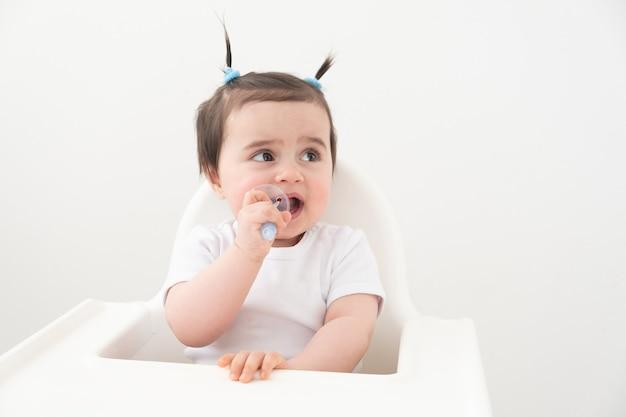 Schattige babymeisje glimlachend en haar tanden poetsen met een gekleurde borstel