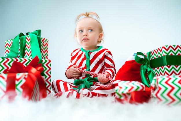 Schattige babymeisje in de buurt van kerstmuts poseren op kerst achtergrond met decoratie. zittend op de vloer met kerstbal.