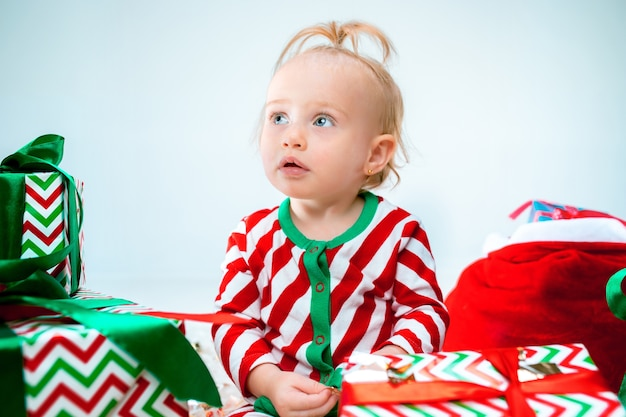 Schattige babymeisje in de buurt van kerstmuts poseren op kerst achtergrond. zittend op de vloer met kerstbal. vakantie seizoen.