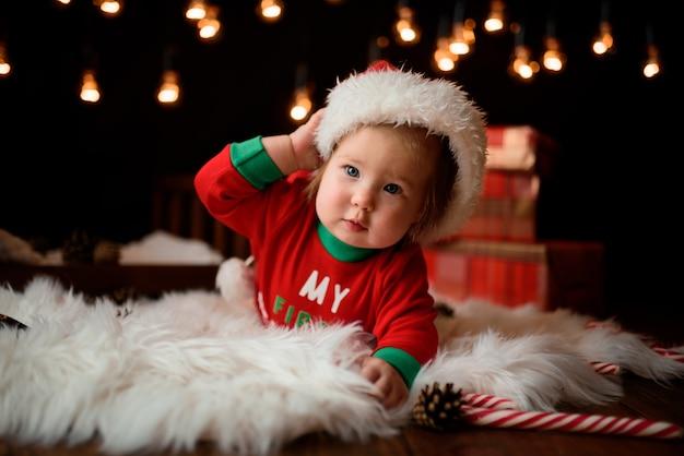 Schattige babymeisje in een rode kerst kostuum met retro slingers zit op een vacht