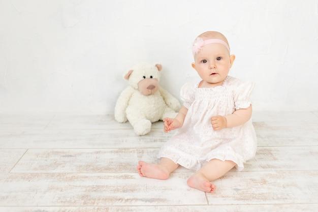 Schattige babymeisje in een witte jurk zit zes maanden met speelgoed op de grond