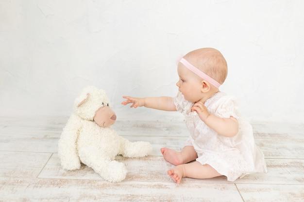 Schattige babymeisje in een witte jurk zit zes maanden voor een speelgoedbeer op de vloer en speelt ermee