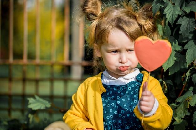 Schattige babymeisje in herfst park lollipop eten.
