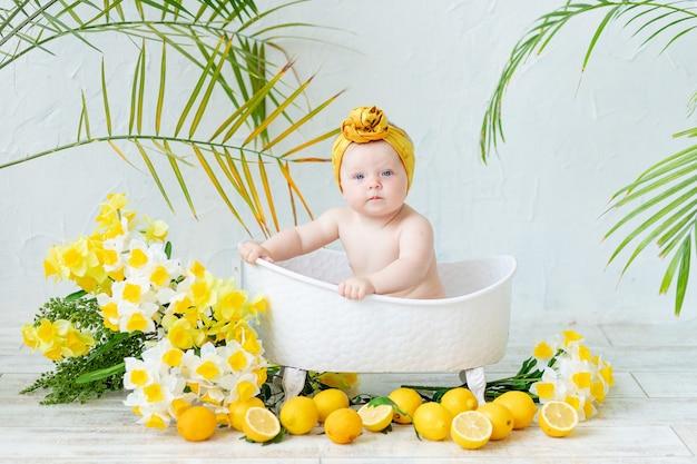 Schattige babymeisje in het bad baadt in een gele hoed met bloemen narcissen en citroenen, het concept van hygiëne en kinderopvang
