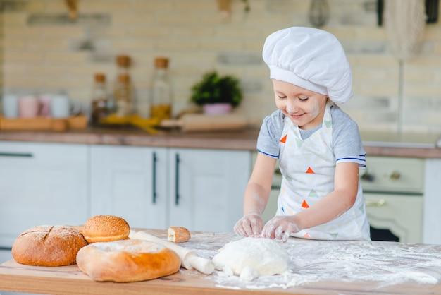Schattige babymeisje in kostuum kookt koken in de keuken