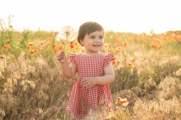 Schattige babymeisje in rode jurk met grote paardebloem op veld van papavers bij zomer zonsondergang summer