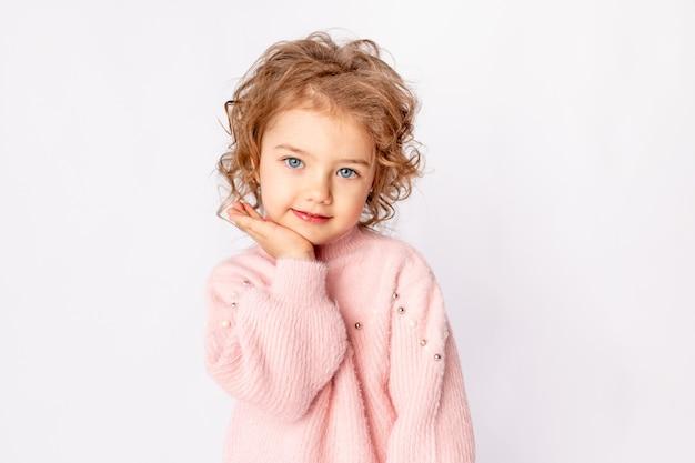 Schattige babymeisje in roze winterkleren op witte achtergrond, ruimte voor tekst
