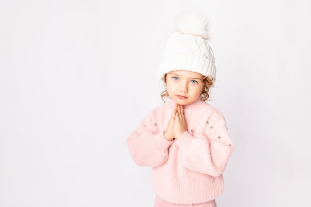 Schattige babymeisje in roze winterkleren op witte achtergrond