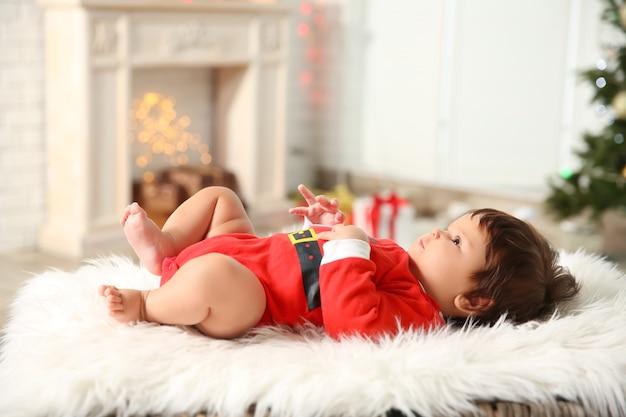 Schattige babymeisje in santa claus kostuum liggend op plaid thuis