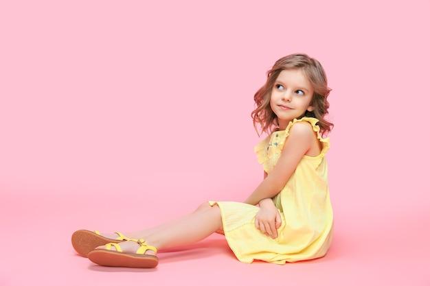 Schattige babymeisje jaar oud dragen trendy gele jurk zittend in de kamer over roze