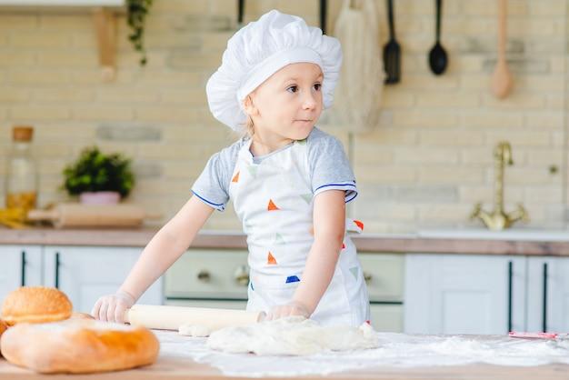 Schattige babymeisje koken in huis keuken
