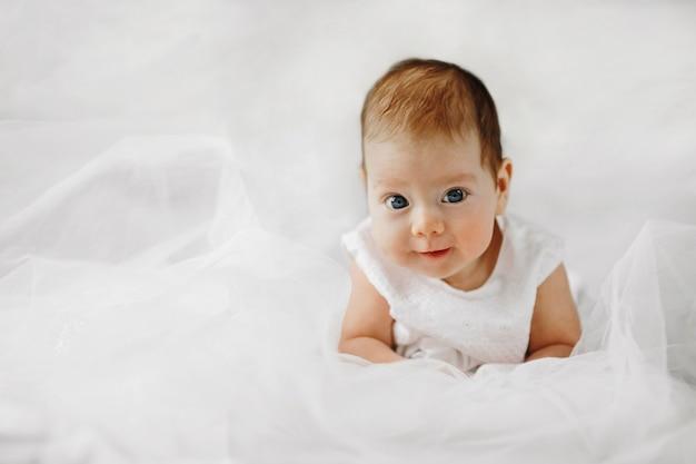 Schattige babymeisje ligt op de buik met geopende grote blauwe ogen, gekleed in witte outfit