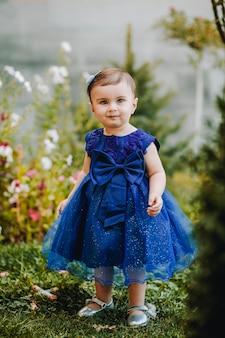 Schattige babymeisje met blauwe jurk staande op het gras in de tuin met veel bloemen