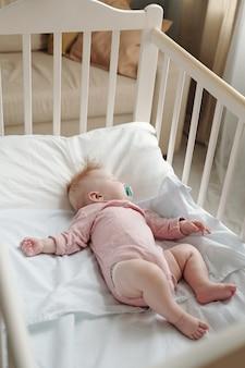 Schattige babymeisje met fopspeen in mond slapen in de wieg
