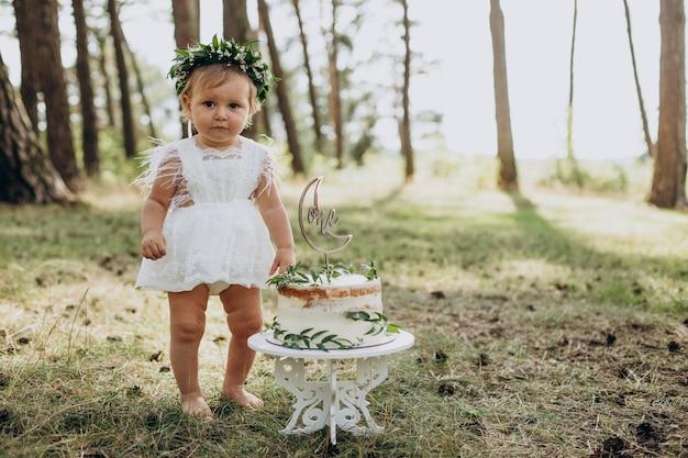 Schattige babymeisje met haar eerste verjaardagstaart