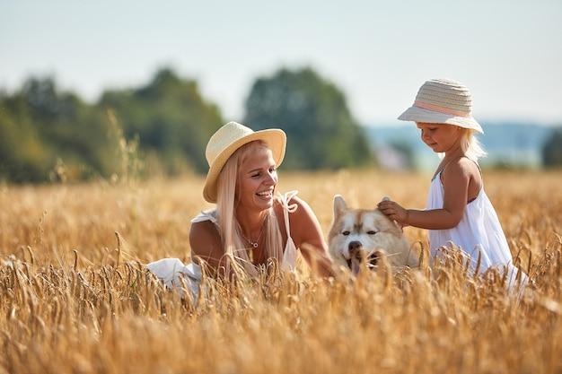 Schattige babymeisje met moeder en hond op tarweveld. gelukkig jong gezin geniet van tijd samen in de natuur