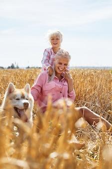 Schattige babymeisje met moeder en hond op tarweveld. gelukkig jong gezin genieten van tijd samen in de natuur. moeder, babymeisje en hond husky buiten rusten. saamhorigheid, liefde, geluk concept.
