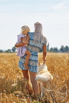 Schattige babymeisje met moeder en hond op tarweveld. gelukkige jonge familie genieten van tijd samen in de natuur. moeder, babymeisje en hond husky rusten buiten. saamhorigheid, liefde, geluk concept.
