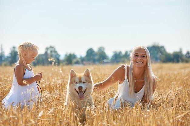 Schattige babymeisje met moeder en hond op tarweveld