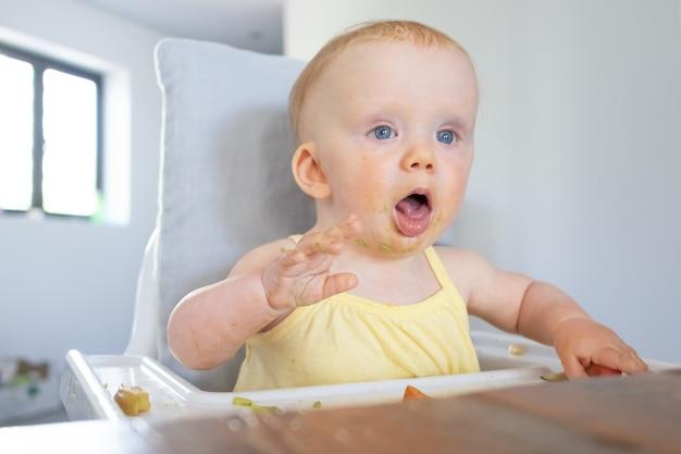 Schattige babymeisje met puree vlekken op gezicht zittend in kinderstoel met rommelig voedsel op dienblad, mond openen en tong tonen. gorgelen reflex of kinderopvang concept