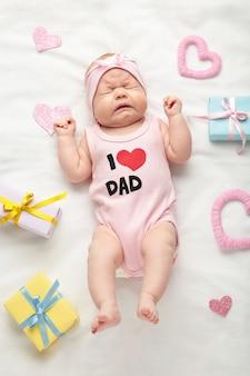 Schattige babymeisje niezen op wit. valentijnsdag