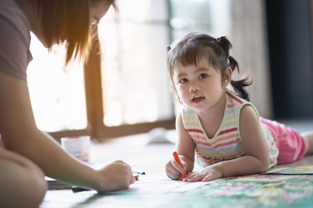 Schattige babymeisje schilderen met haar moeder in het huis