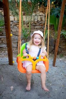Schattige babymeisje schommelt op een schommel en lacht in de zomer in een panamahoed