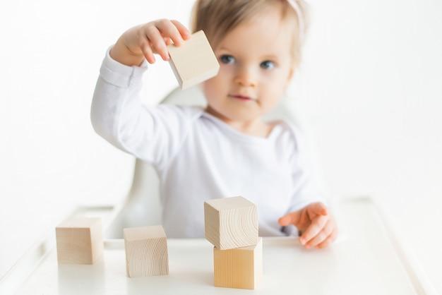 Schattige babymeisje spelen met houten kubussen. klein kind gebouw toren. bouwblok voor kinderen. montessori educatieve methode. selectieve aandacht