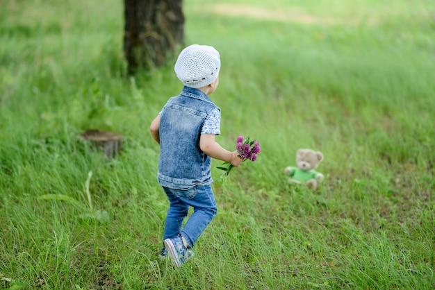 Schattige babymeisje wandelen in prachtig park met kleurrijke bloem op zomerseizoen hij glimlachend en gelukkig permanent buiten natuur achtergrond.