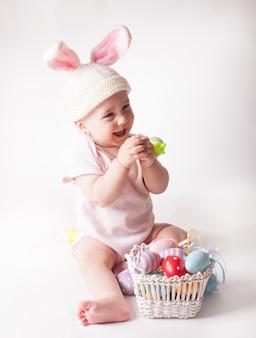 Schattige babymeisje zit in een gebreide konijn hoed geïsoleerd op wit