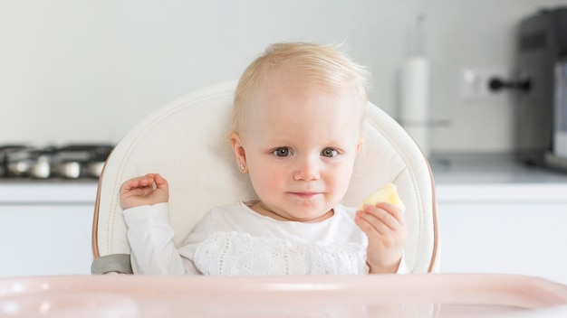 Schattige babymeisje zit in kinderstoel