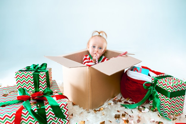 Schattige babymeisje, zittend in doos op kerst achtergrond. vakantie, feest, kind concept