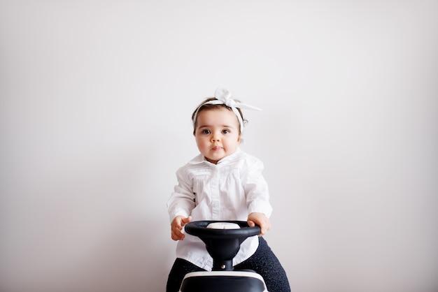Schattige babymeisje, zittend op een kleine fiets. leren fietsen.