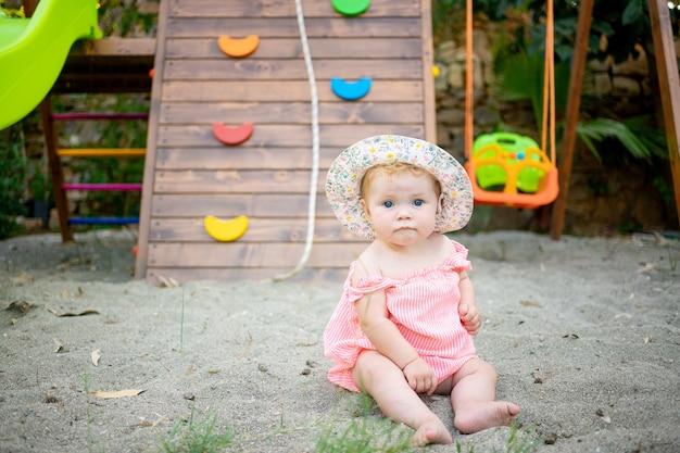 Schattige babymeisje zittend op het zand op de speelplaats in de zomer in een panama hoed en blote voeten