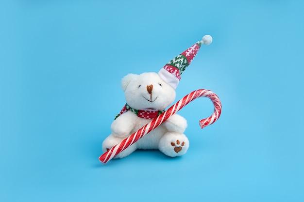 Schattige beer in een kerstmuts speelgoed houdt een lolly in zijn poten.