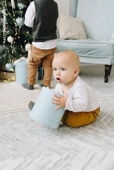 Schattige blanke baby spelen met een verpakt kerstcadeau