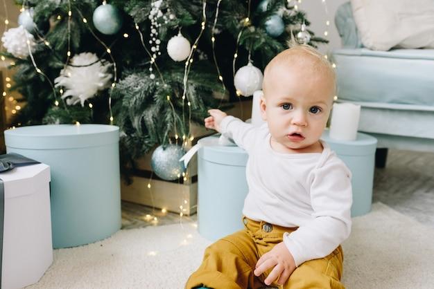 Schattige blanke baby zitten in de buurt van kerstboom omgeven door cadeautjes